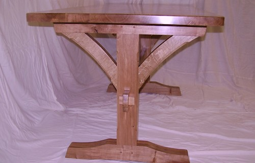 A writing desk in sycamore with curved cherry legs.
